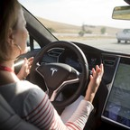 A woman holds her hands off the steering wheel of a Tesla Model S demonstrating Autopilot features.