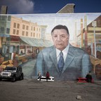 A mural on the side of a building shows a man standing in a city street.