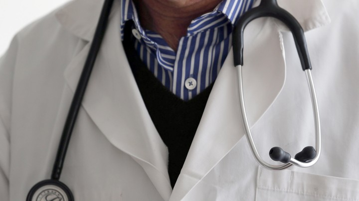 A photo-illustration shows a French general practitioner with a stethoscope in a doctor's office in 2015.