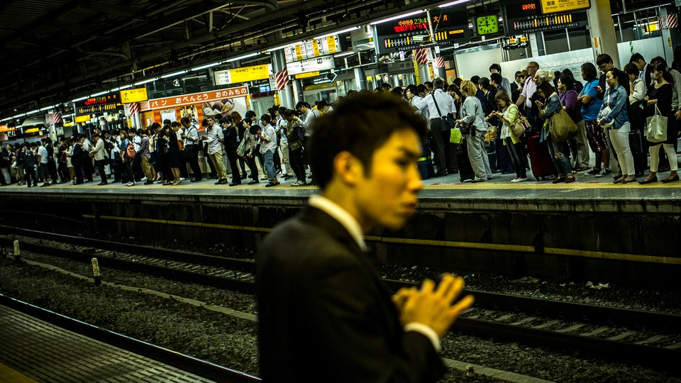 A Japanese man stands in a crowded subway station.
