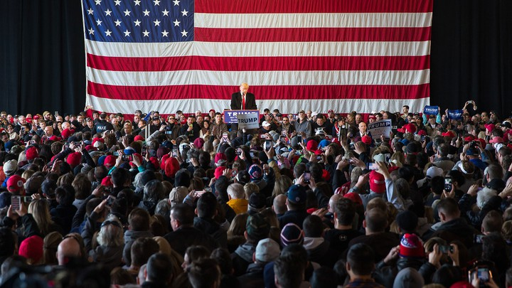 Donald Trump addresses a crowd of supporters with a large American flag behind him.