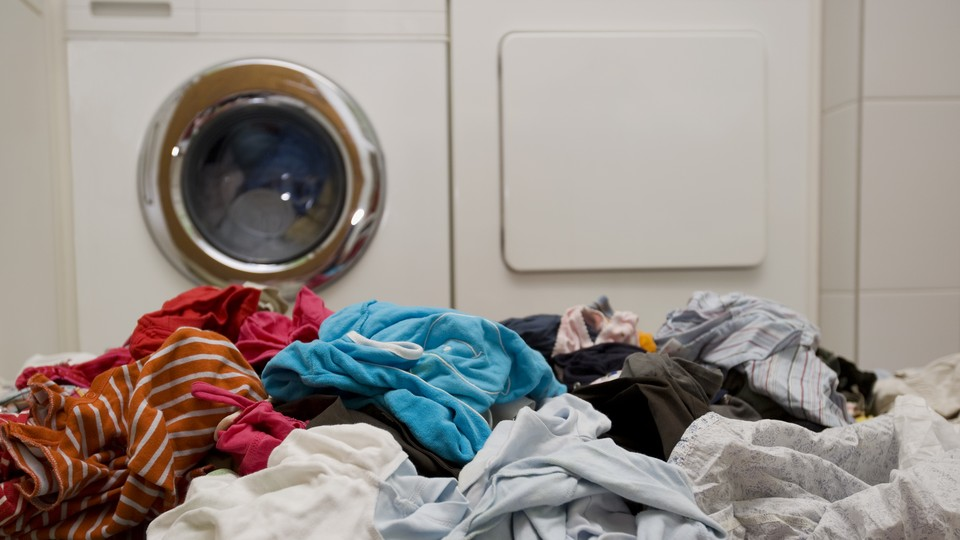 A pile of laundry in front of a washing machine