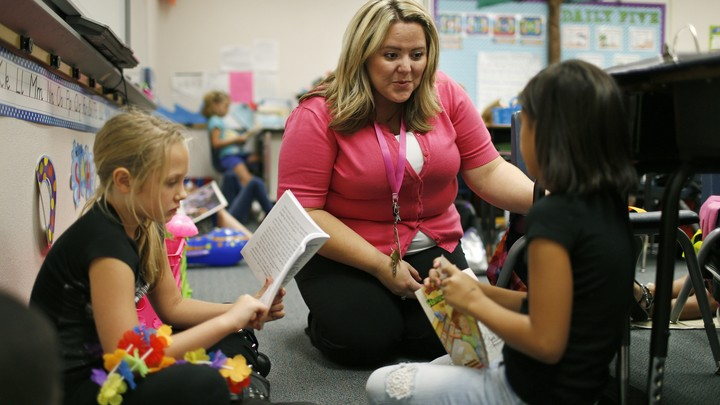 A substitute teacher sits on the floor with students as they read.