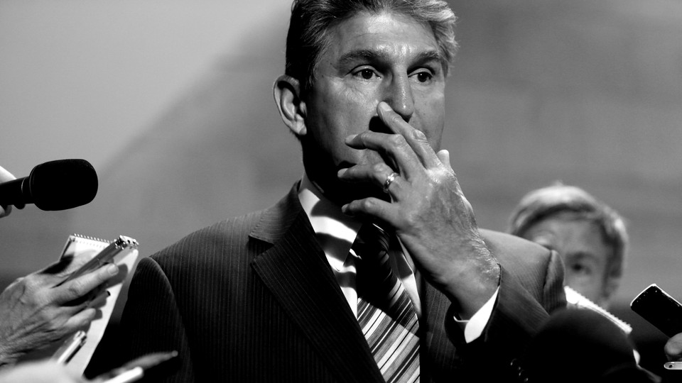 Joe Manchin stands amid reporters, covering his mouth with his hand.