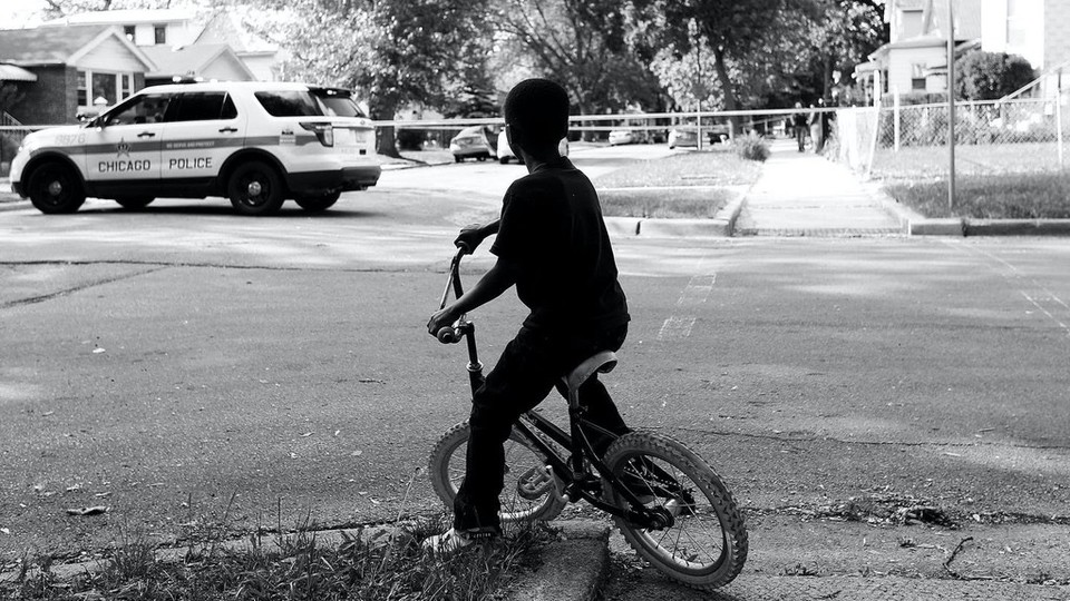 Child on a bike with a police car in the background.