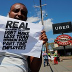 A man protesting Uber driver wages holds up a sign.