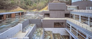 A modern museum building with a series of sunken terraces in Japan.