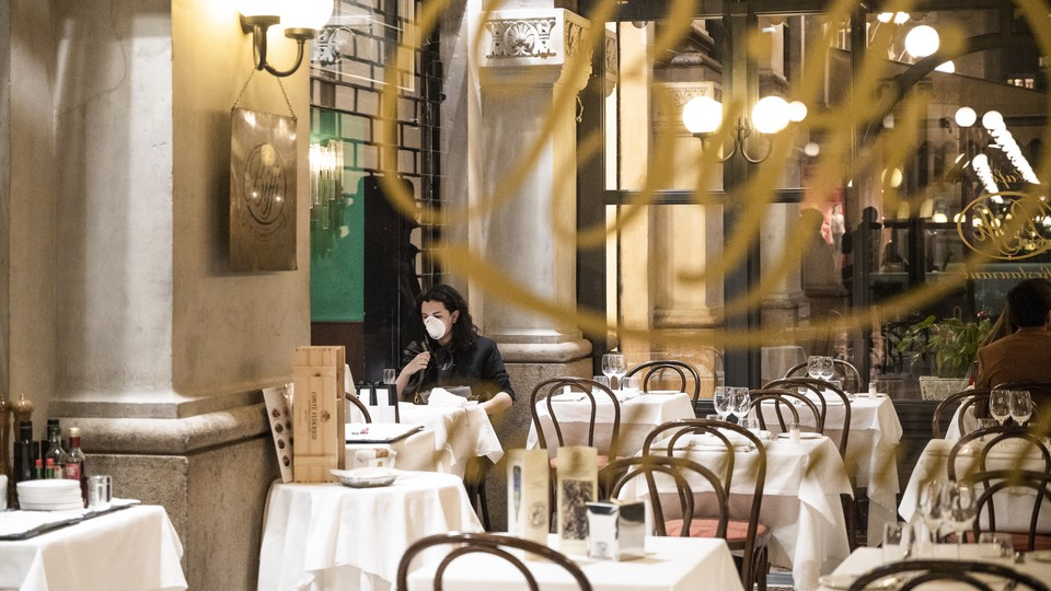 A tourist wears a protective mask at Biffi restaurant in Milan, Italy.