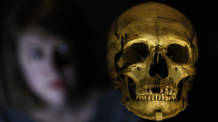 A woman looks at a human skull.