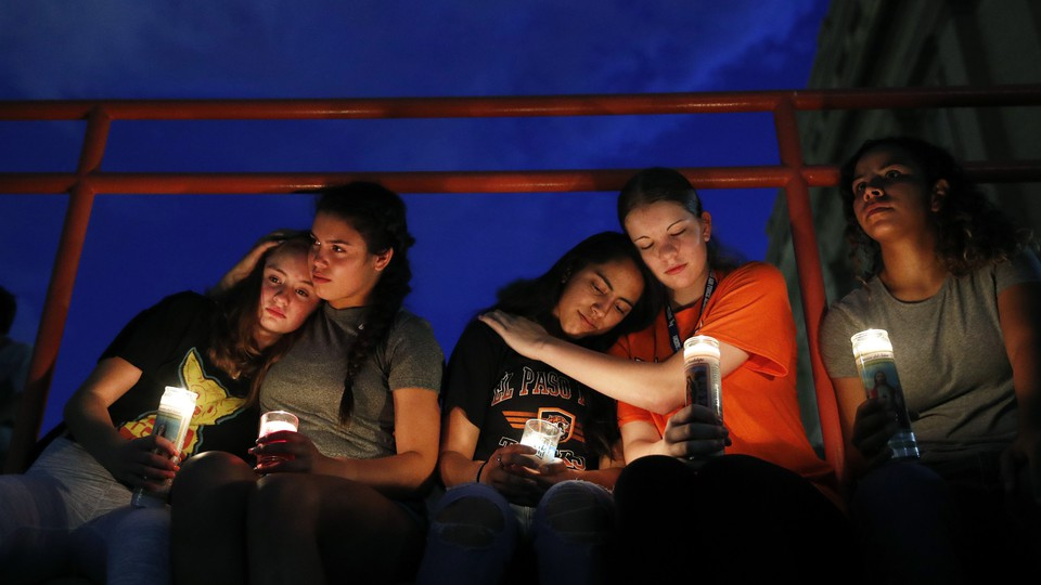 Young women comfort each other at a vigil in El Paso.