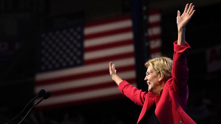 Elizabeth Warren waves to a crowd in front of an American flag.