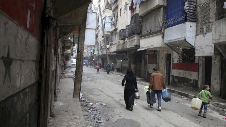 Civilians walk down a street in Aleppo, Syria, on August 11.