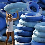 A girl carries an inflatable tube.
