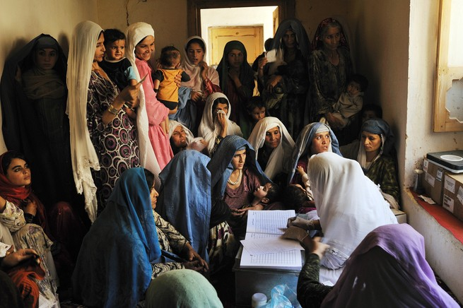 Women packed tightly together listen to a woman talk in a small room.