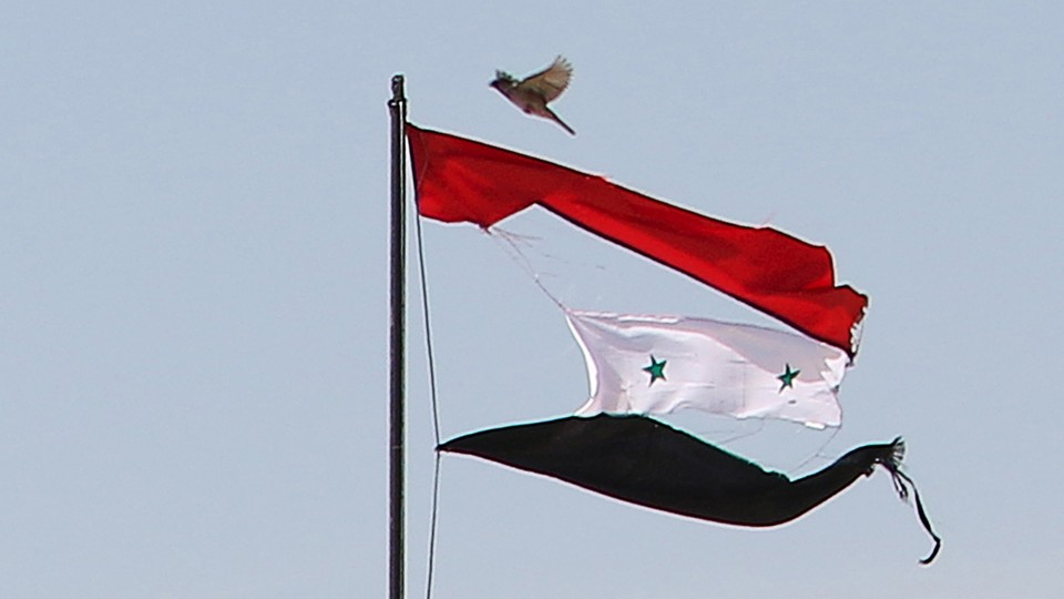 A tattered Syrian flag waves in the northeastern city of Qamishli, Syria.
