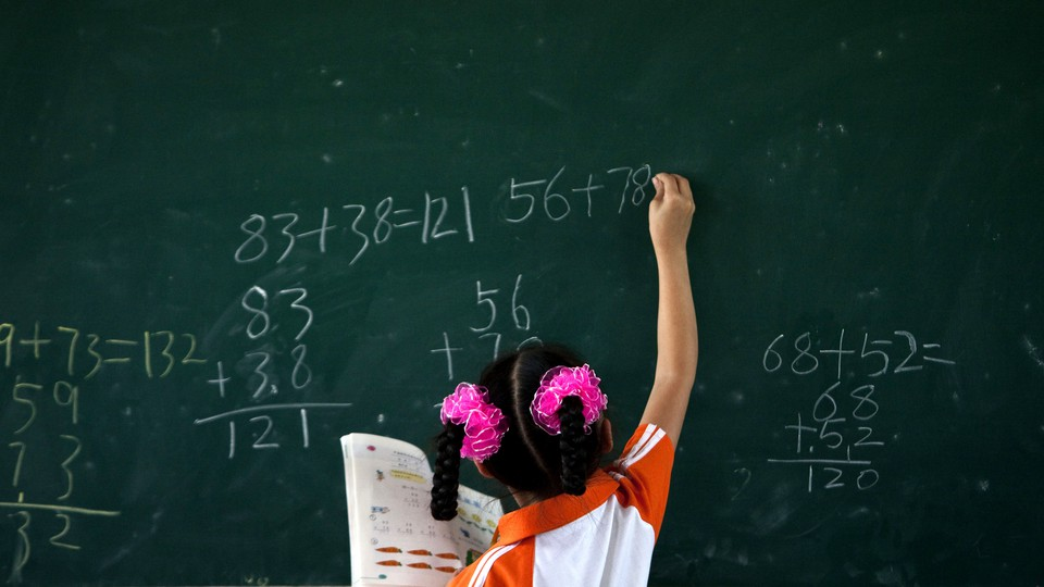 A girl wearing pigtails does math problems on a chalkboard