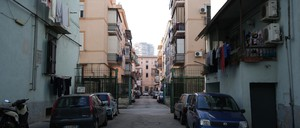 A narrow Italian street flanked by four-story apartment buildings painted blue and pink.