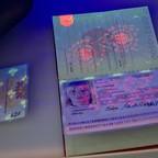UV lights illuminate security features of a German passport.