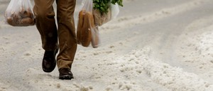 A man carries plastic bags filled with food through the snow.