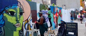 Two women painting colorful panels outdoors with other artists in the background
