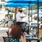 photo: A masked server in the outside dining area of a restaurant in St. Petersburg, Florida on May 4.
