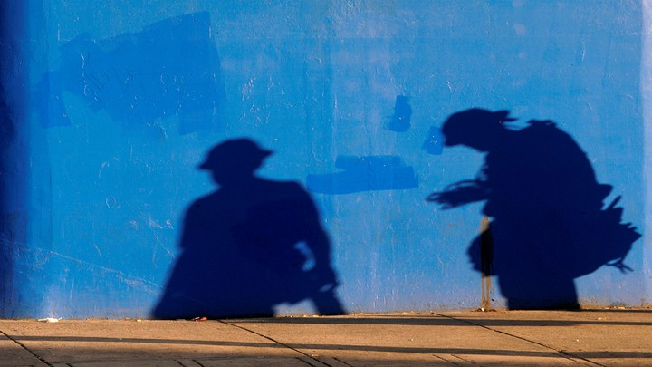 The shadows of construction workers against a plain blue wall