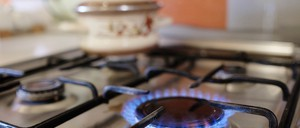 A gas stovetop with one burner lit.