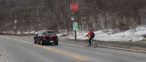 a photo of a cyclist and a car on Mount Royal Park in Montreal