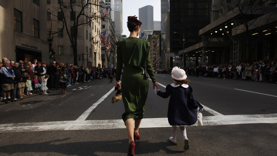 The backs of a mother and daughter, walking hand-in-hand down a street in New York City