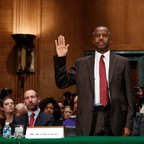 Ben Carson stands with his right hand raised in a packed hearing room.