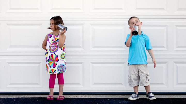 Two children talk with tin-can telephones.