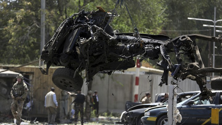 U.S. soldiers lift car wreckage with a crane in Kabul, Afghanistan.