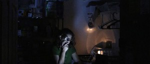 A woman looks at her phone in near darkness
