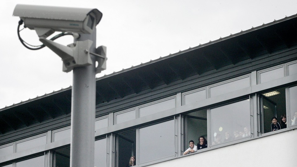 A mounted security camera outside a school with students looking out the window