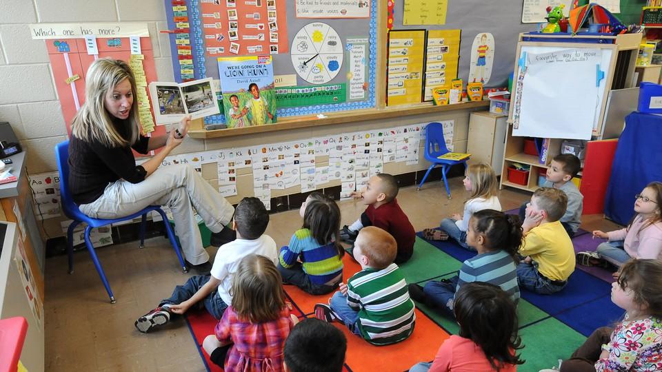 A teacher reads to sitting schoolchildren