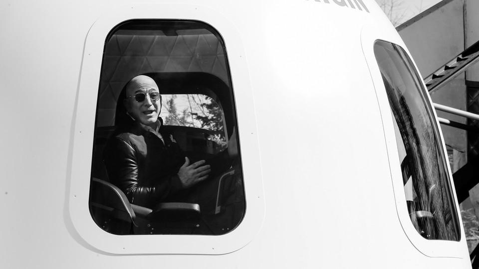 A photo of Jeff Bezos wearing sunglasses inside a Blue Origin capsule