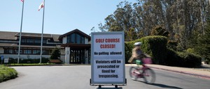 photo: A cyclist rides past a closure sign at an entrance to the Presidio Golf Course in San Francisco.