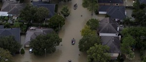 Aerial photo of a flooded residential neighborhood with rescue boats in the streets.