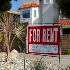 """A """"For Rent"""" sign is posted outside a small apartment complex in Carlsbad, California"""