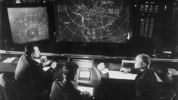 A black-and-white photograph of a group of people looking at a screen displaying a map of the United States
