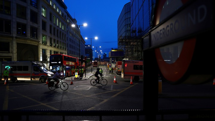People cycle past a police cordon on the north side of London Bridge in London.