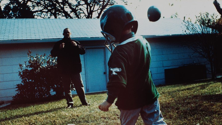 A father and son play football.