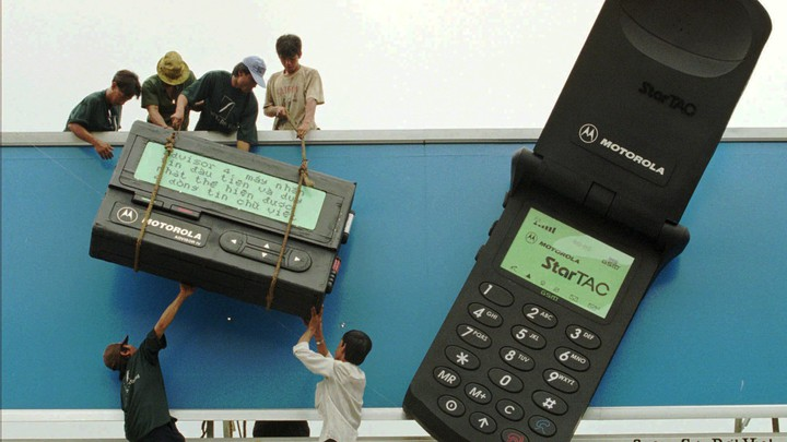 Workers hoist a giant Motorola cellphone and pager onto a billboard.