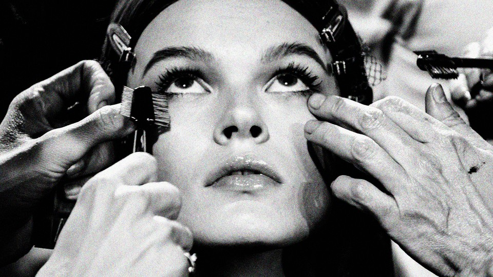 A close up of a woman having make up applied to her face
