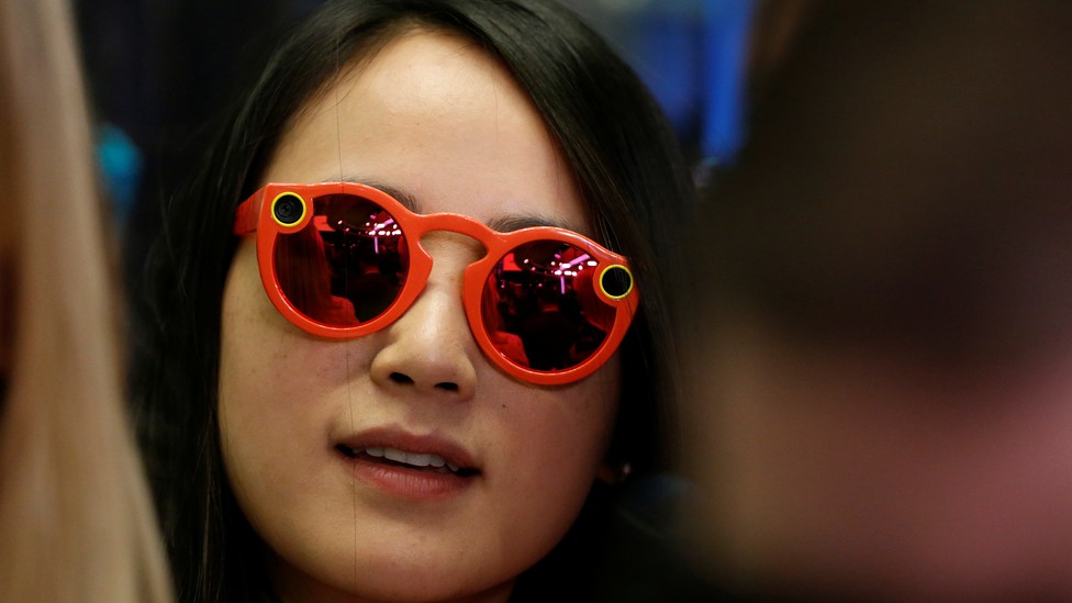 A woman wears bright red Snapchat Spectacles, glasses made by the popular app, on the floor of the New York Stock Exchange, on March 2, 2017.