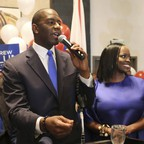 Florida politician Andrew Gillum and his wife at a victory party with signs and balloons.