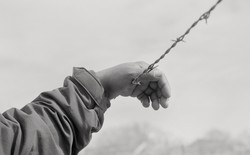 Raul Rodriguez's hand rested on barbed wire in black and white.