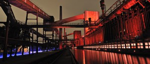 The exterior of a former factory lit up by red and purple lights