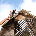 A man elevated by crane works on the roof of a partially deconstructed house.