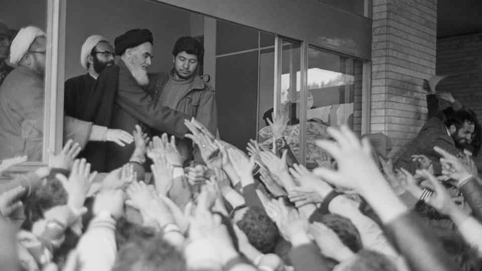 Ayatollah Ruhollah Khomeini greets a crowd of people waving their hands at him at Tehran University in 1979.